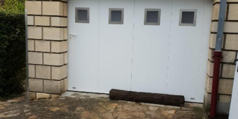 Porte sectionnelle latérale avec hublots et portillon pivotant